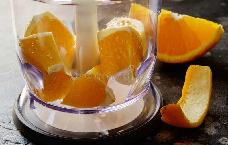 Licuadora con las naranjas, rebanada de naranja en la tabla imagen de archivo libre de regalías
