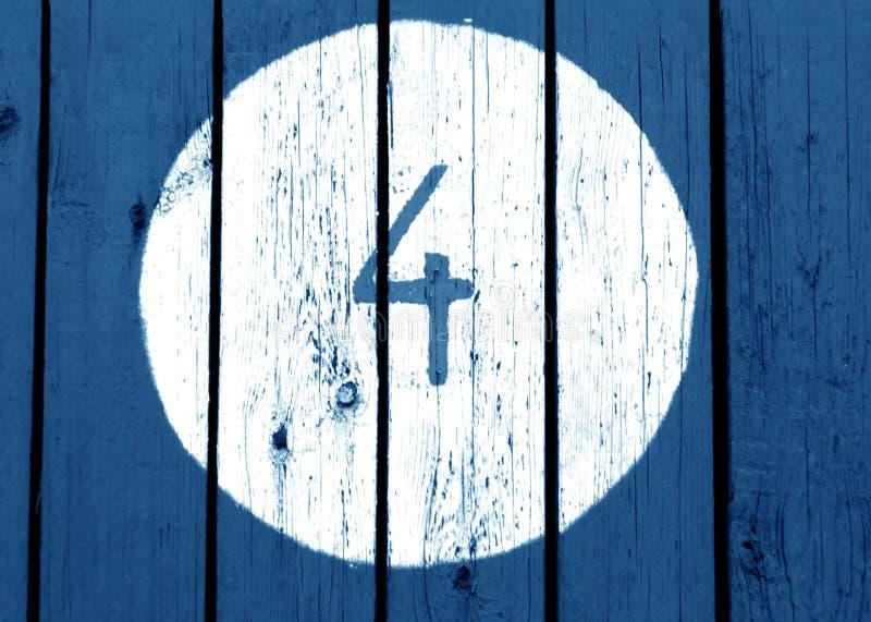 Liczba cztery na błękit stonowanej drewnianej ścianie obraz royalty free