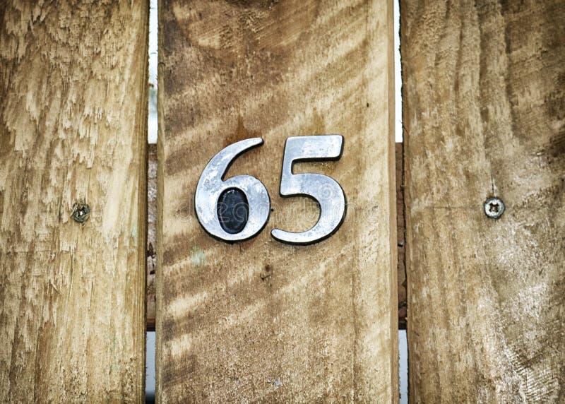 Liczba sześćdziesiąt pięć na drewnianej bramie obrazy royalty free