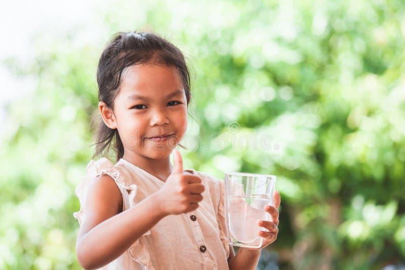 ?liczna azjatykcia dziecko dziewczyna lubi pi? wod? i trzyma? szk?o ?wie?a woda zdjęcia royalty free