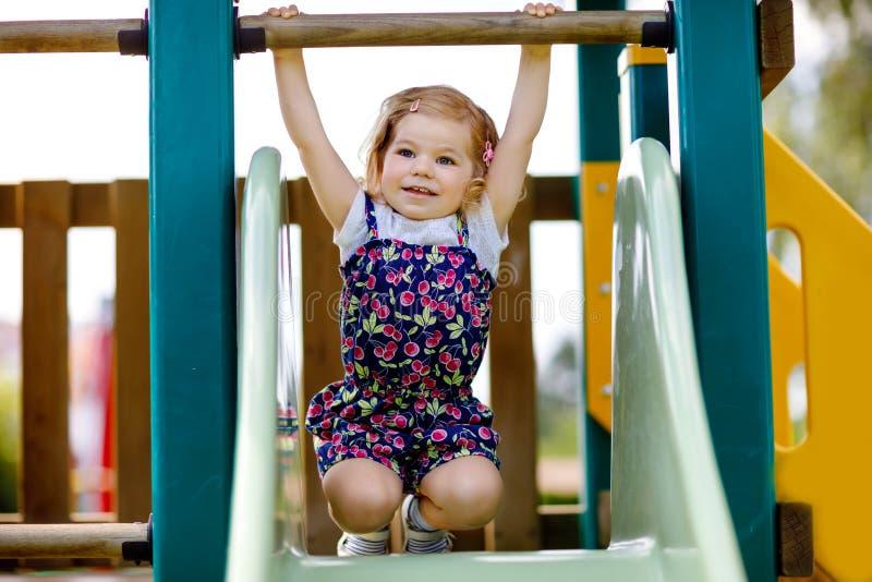 ?liczna berbe? dziewczyna bawi? si? na obruszeniu na plenerowym boisku Piękny dziecko w kolorowych skrótów spodniach ma zabawę na zdjęcia stock