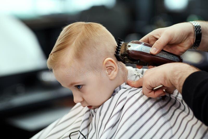?liczna blond ch?opiec z niebieskimi oczami w fryzjera m?skiego sklepie ma ostrzy?enie fryzjerem R?ki stylista z narz?dziami zdjęcie royalty free