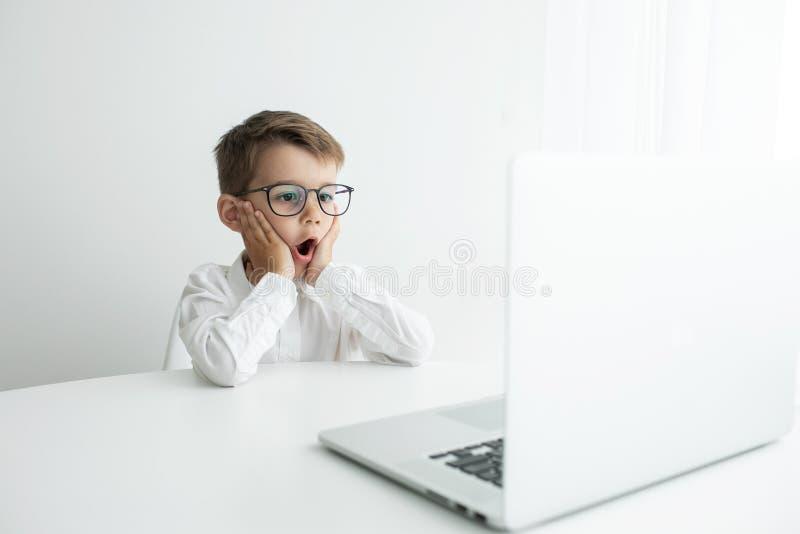 ?liczna ch?opiec u?ywa laptop podczas gdy robi? pracie domowej przeciw bia?emu t?u zdjęcia royalty free