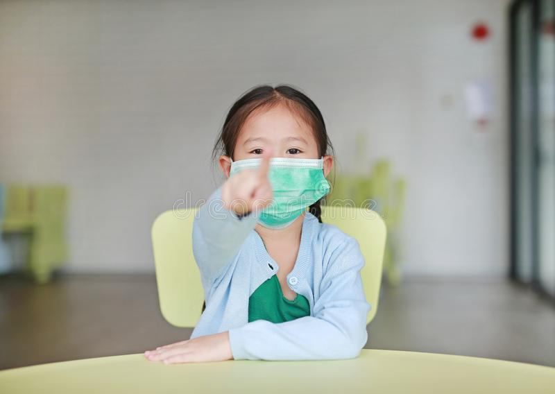 ?liczna ma?a Azjatycka dziecko dziewczyna jest ubranym ochronn? mask? z wskazywa? przy tob? siedzi na dzieciaka krze?le w dziecko zdjęcie stock