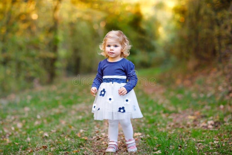 ?liczna ma?a berbe? dziewczyna robi spacerowi przez jesie? parka Szcz??liwy zdrowy dziecko cieszy si? chodzi? z rodzicami Pogodny zdjęcie royalty free