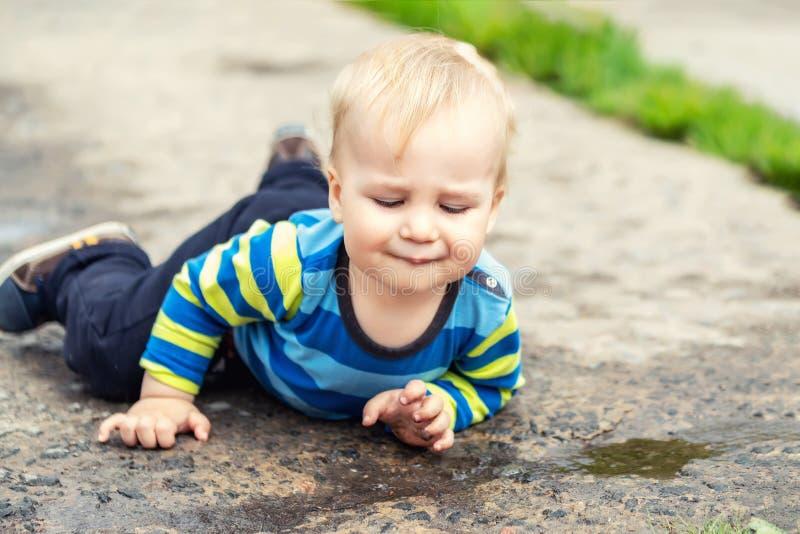 ?liczna ma?a caucasian blond berbe? ch?opiec ma zabawy lying on the beach w ka?u?y po deszczu outdoors Ciekawy dziecko odkrywa ?w obraz stock