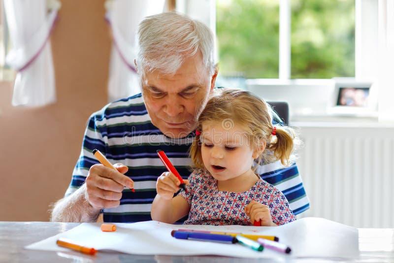 ?liczna ma?a dziecko berbecia dziewczyna i przystojny starszy dziadek obraz z kolorowymi o??wkami w domu Wnuk i m??czyzna fotografia royalty free