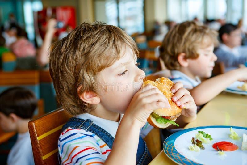?liczna zdrowa preschool ch?opiec je hamburgeru obsiadanie w szkolnej bak?aszce zdjęcia royalty free