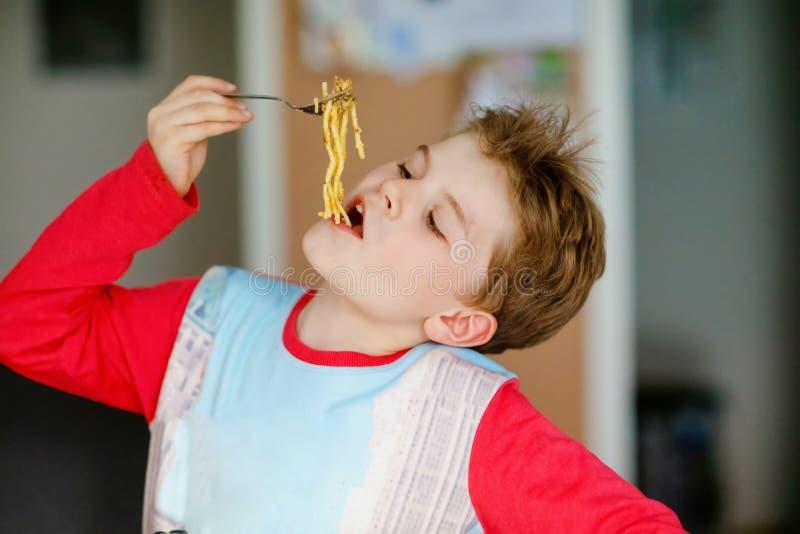 ?liczna zdrowa preschool dzieciaka ch?opiec siedzi w szko?y lub pepiniery kawiarni je makaron?w kluski Szcz??liwy dziecko je zdro obraz royalty free