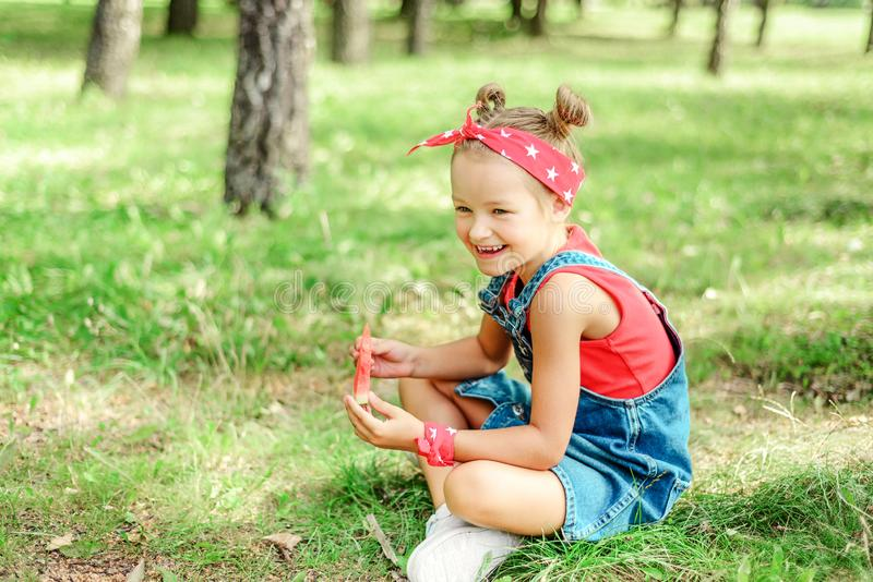 ?licznej ?asowania dziewczyny ma?y arbuz dziecko w drelichowym kostiumu i czerwonym szaliku na jego głowie obrazy stock