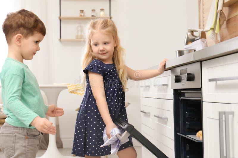 ?liczni dzieci piec ciastka w piekarniku obrazy royalty free