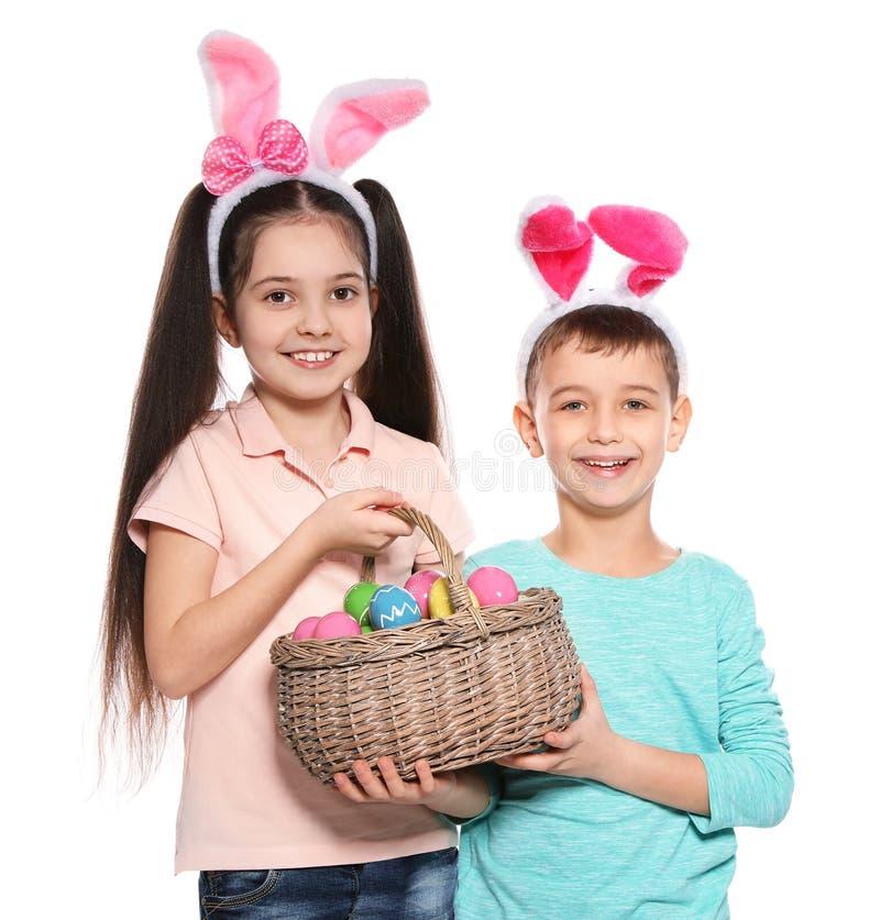 ?liczni dzieci trzyma koszykowy z Wielkanocnymi jajkami na bielu w kr?lik?w ucho kapita?kach obrazy stock