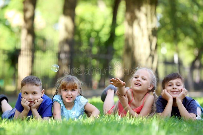?liczni ma?e dzieci k?ama na zielonej trawie w parku obrazy stock
