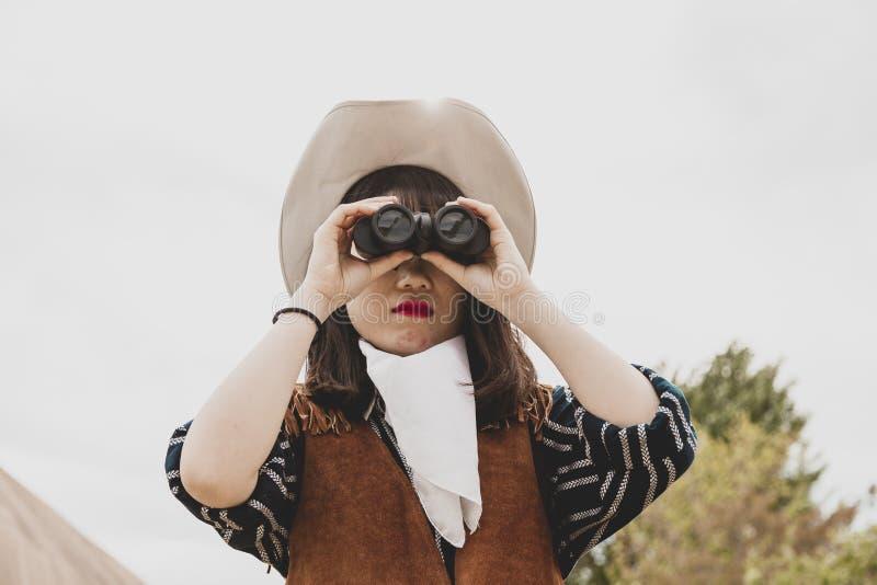 ?liczny chi?ski cowgirl podczas gdy patrzej?cy horyzont z lornetkami fotografia royalty free