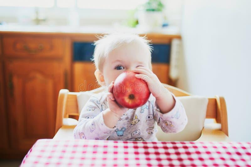 ?liczny dziewczynki ?asowania jab?ko w kuchni zdjęcie stock