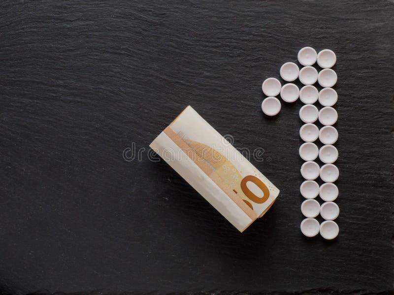 Liczy jeden znaka robić od białych medycznych pigułek i niektóre gotówki, pojęcie opieki zdrowotnej kosztu pieniądze, kopii przes obraz royalty free