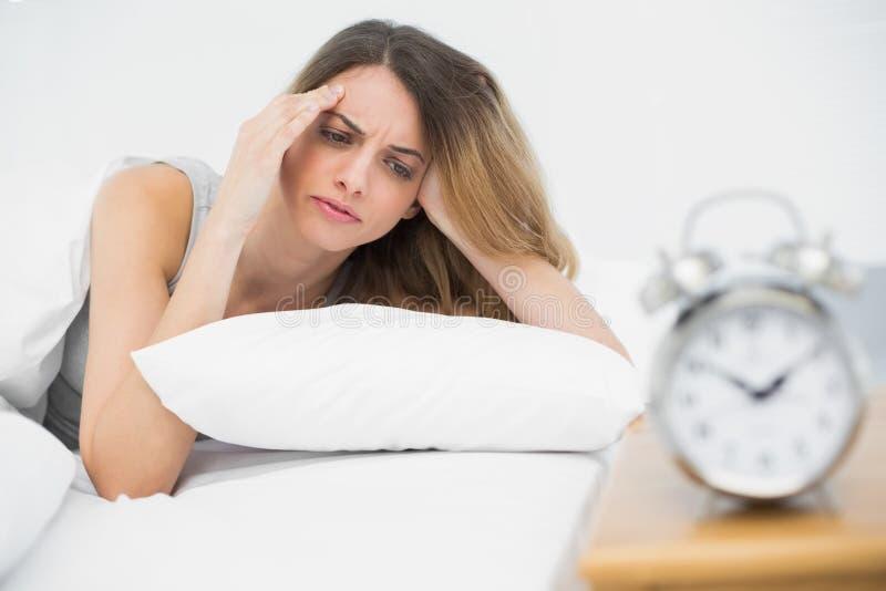 Lida den unga kvinnan som har huvudvärken som ligger på hennes säng arkivbild