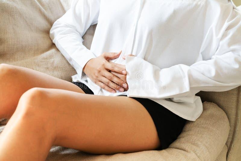 Lidande för den unga kvinnan från buk- smärtar, medan sitta på soffan och det känsliga magknipet, tecken av pms arkivbild