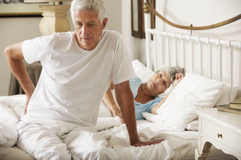 Lidande för hög man från ryggvärken som får ut ur säng royaltyfri bild