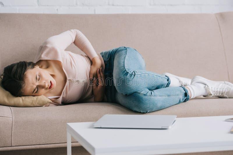 lidande för ung kvinna från mageknip, medan ligga på soffan royaltyfria bilder