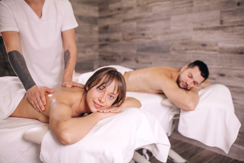 Lidande för ung man och kvinnafrån scoliosis som får massage fotografering för bildbyråer