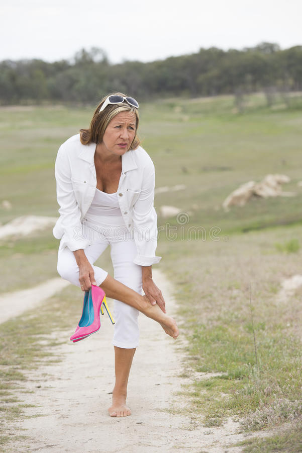 Lidandekvinna i höga häl med öm fot arkivfoton