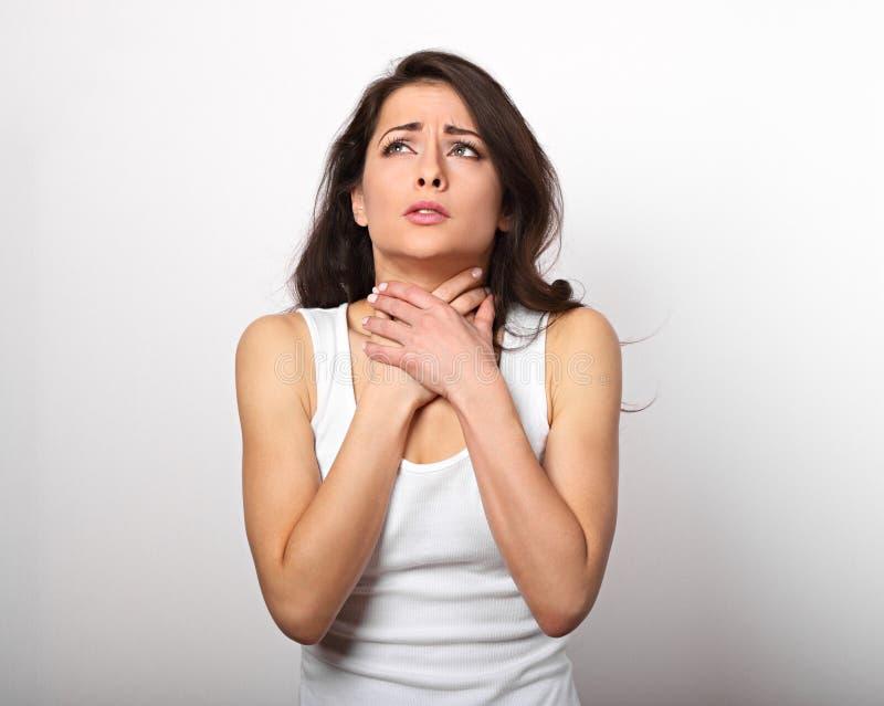Lidandekvinnan som rymmer halsen med mycket starkt, smärtar och unh royaltyfri foto