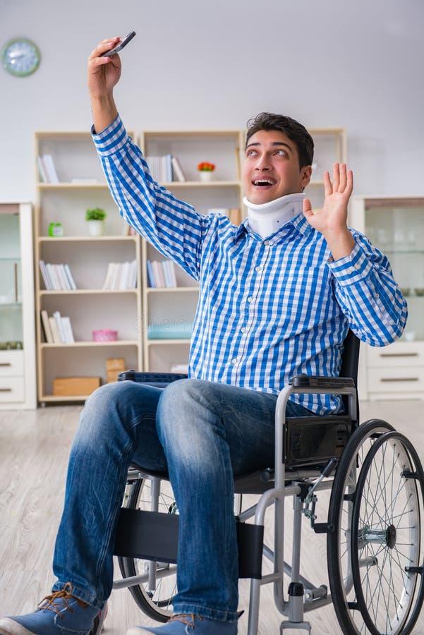 Lidandet för ung man från skada på rullstolen hemma arkivfoto