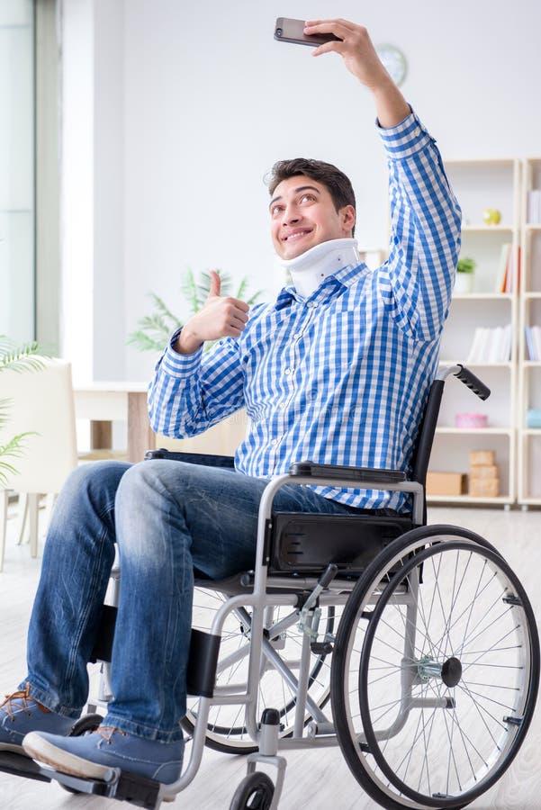 Lidandet för ung man från skada på rullstolen hemma arkivbild