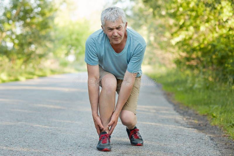 Lider den attraktiva gråa haired äldre mannen dragna muskeln av benet, från smärtar, kan ` t fortsätta jogga, den iklädda tillfäl arkivbilder