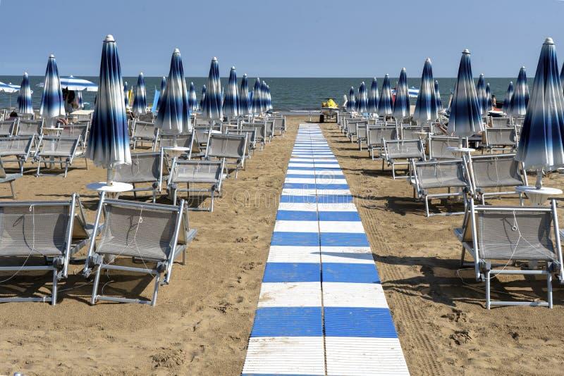 LIDO DI JESOLO, ITALY - May 24, 2019 : Umbrellas on the beach of Lido di Jesolo at adriatic Sea in a beautiful summer day, Italy. On the beach of Lido di royalty free stock image