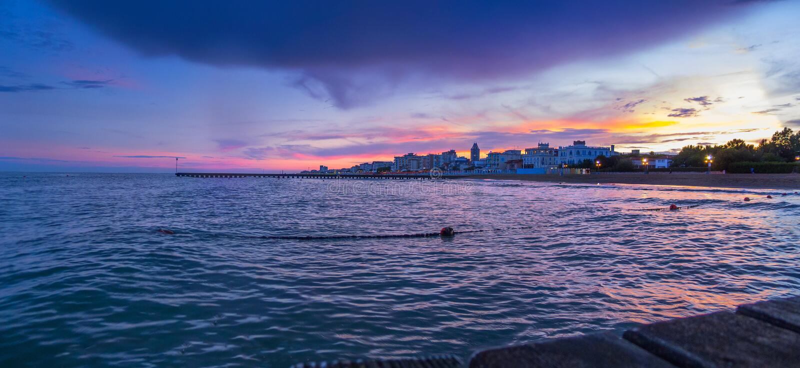 """Lido di Jesolo strand härlig panoramautsikt på för solnedgång†""""från pir till havet med uttrycksfull himmel och moln arkivbild"""