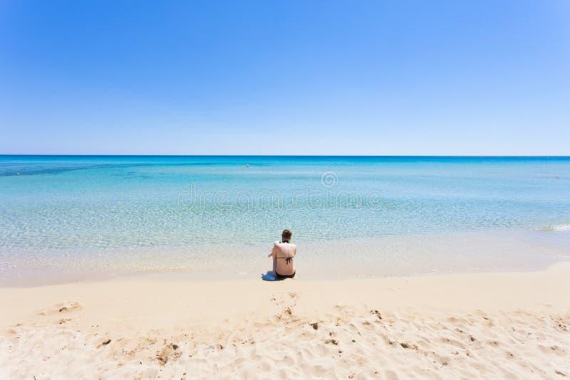 Lido Venere,普利亚-一个年轻母亲坐海滩lookin 库存图片
