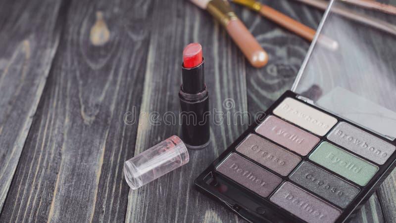 Lidschatten und Lippenstift auf hölzernem Hintergrund stockbild