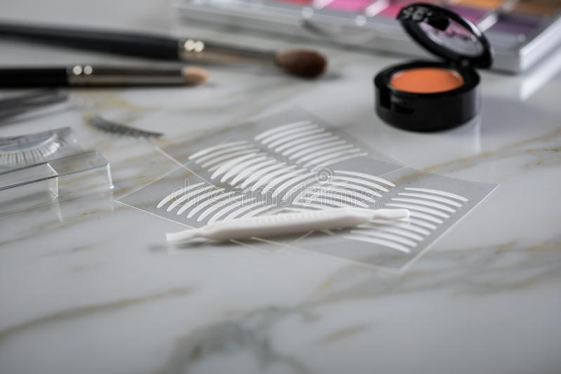 Lidschattenpalette, Bürsten, gefälschte Peitschen, Pinzette und doppelte Bänder der künstlichen Augenlidfalte für Augenmake-up au lizenzfreie stockfotos