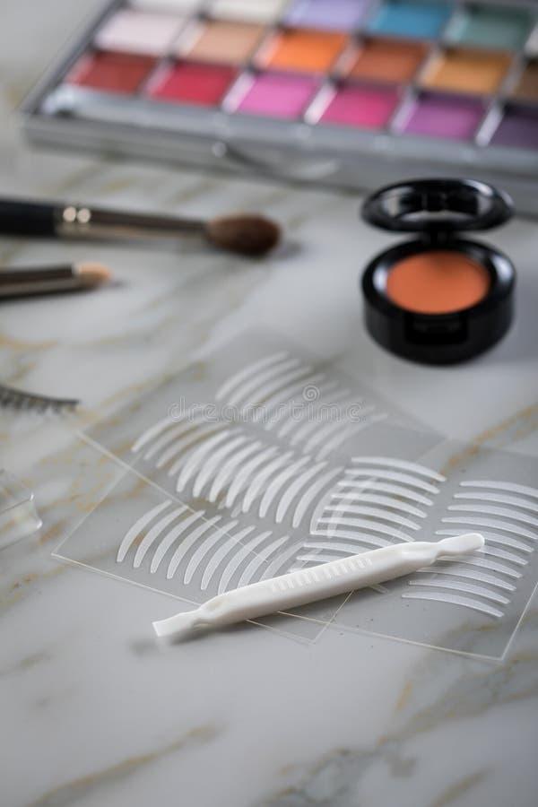 Lidschattenpalette, Bürsten, gefälschte Peitschen, Pinzette und doppelte Bänder der künstlichen Augenlidfalte für Augenmake-up au stockfotografie