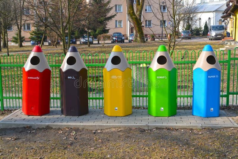 LIDZBARK-VARMINSKI, POLÔNIA Recipientes para o lixo de coleta separado sob a forma dos lápis coloridos fotografia de stock