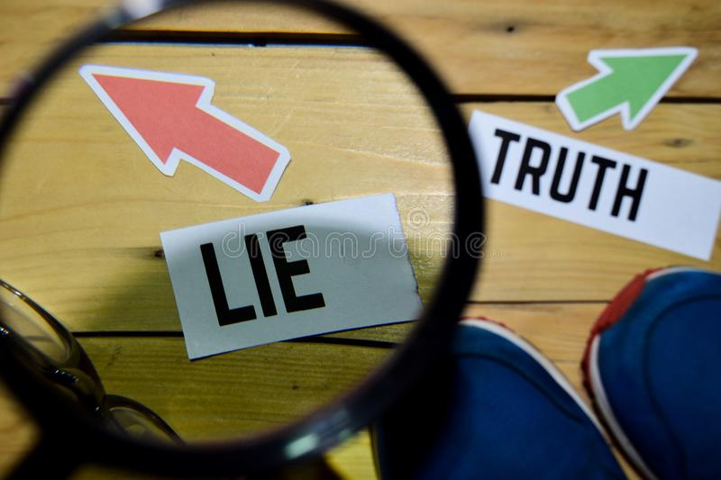 Lie or Truth opposite direction signs in magnifying with sneakers and eyeglasses on wooden. Vintage background. Business and education concepts stock photography