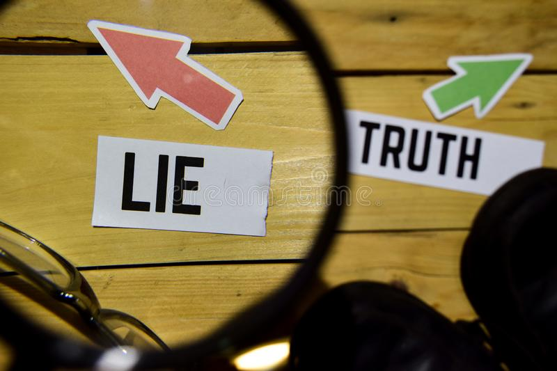 Lie or Truth opposite direction signs in magnifying with sneakers and eyeglasses on wooden. Vintage background. Business and education concepts royalty free stock photo