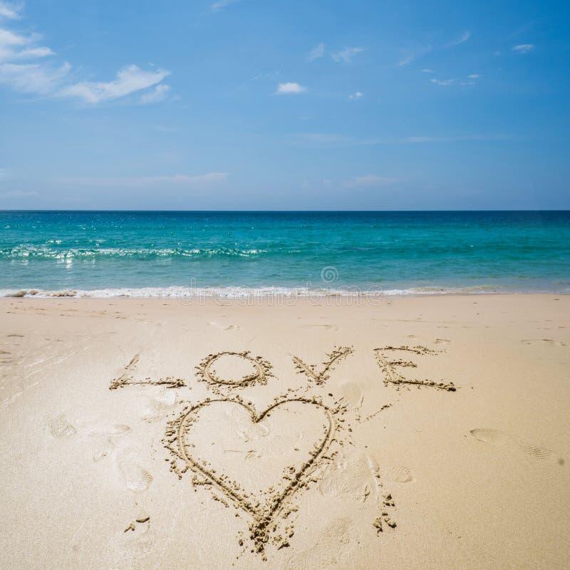 Liebe geschrieben auf den Strand über Meer lizenzfreie stockbilder