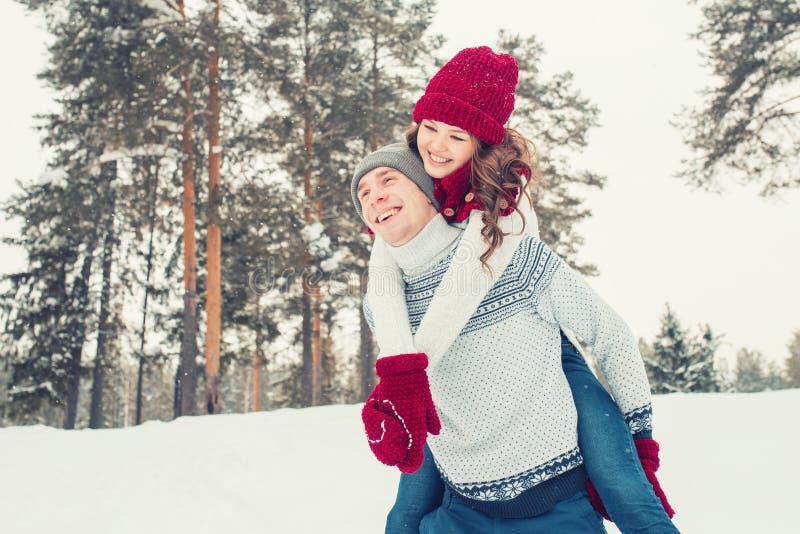 Liebe - glückliches Paar, das lächelndes zusammen lachen des Spaßes an den romantischen Feiertagen hat Junger Mann, der piggyback lizenzfreie stockfotografie