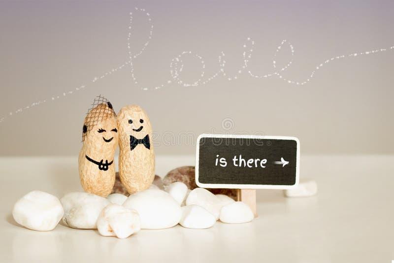 ` Liebe ist dort ` Zwei Erdnüsse mit den gezogenen Gesichtern, die auf rosa Vanillehintergrund umarmen lizenzfreies stockfoto