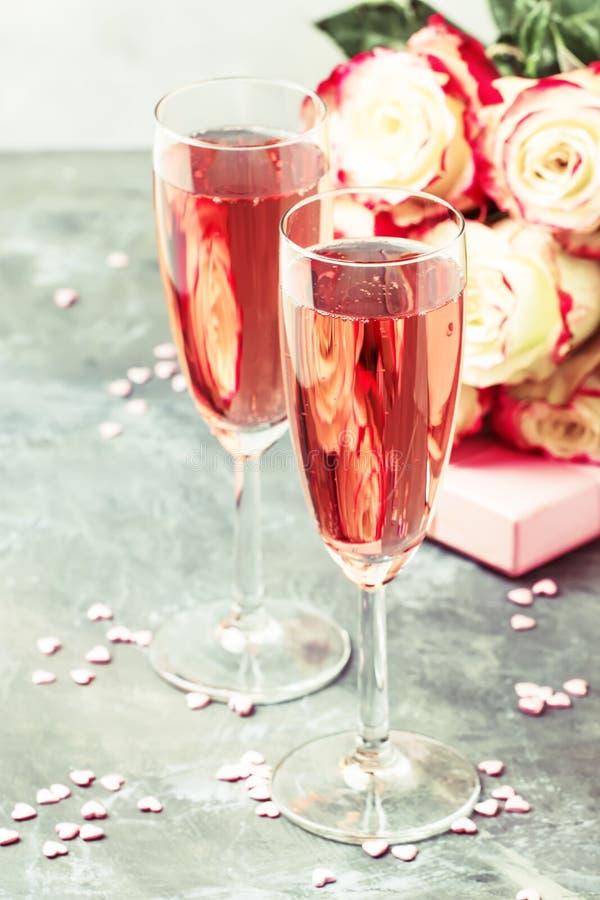 Liebe simbols - Blumenstrauß von weißen und roten Rosen, Geschenkbox, Gläser mit rosa oder rosafarbenem Champagner oder sparcling stockfotografie