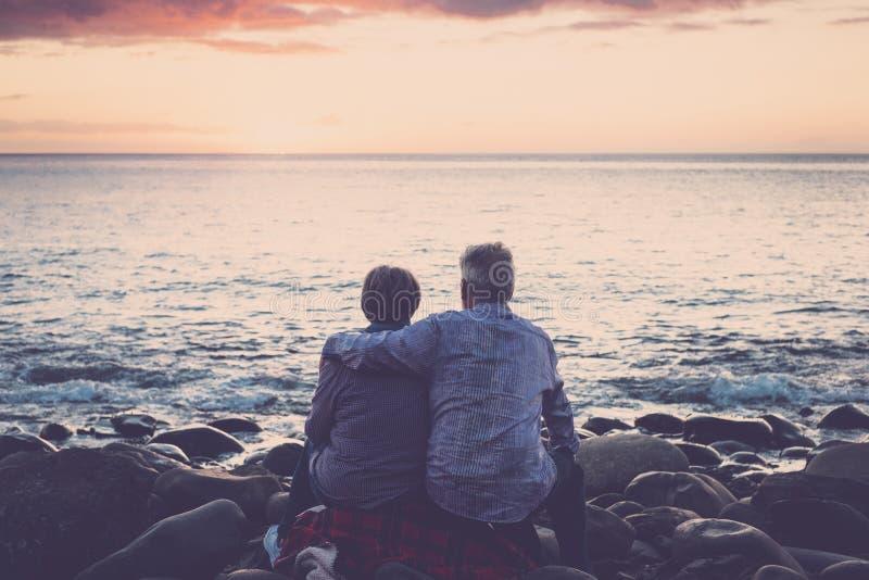 Liebe und Romantik mit Erwachsenem reift - die ?lteren Paare, die das Meer betrachtend bei dem entspannenden Sonnenuntergang sitz lizenzfreie stockbilder