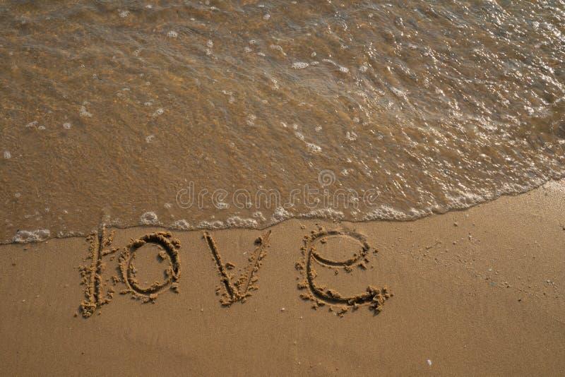 Liebe und Valentinsgrußkonzept Liebeswörter geschrieben in den Sand auf den Strand lizenzfreie stockbilder
