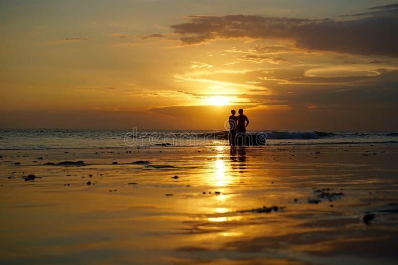 Lieben Sie auf dem Strand im Sonnenuntergang in Bali stockfotos