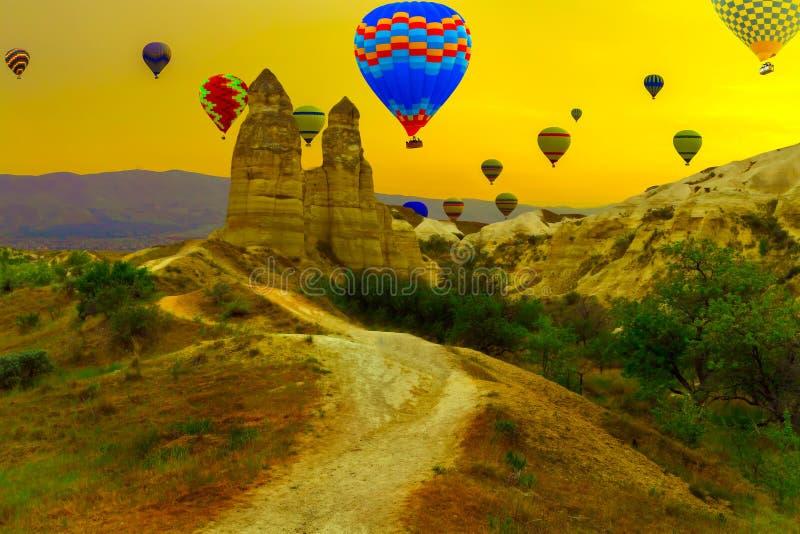 Lieben Sie die Heißluftballone des Tales, die in einem Berg, Landschaft an landen lizenzfreies stockfoto