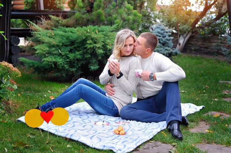 Lieben Sie die Paare, die auf einem Bett im Park sitzen, der ein Picknick hat stockfotografie