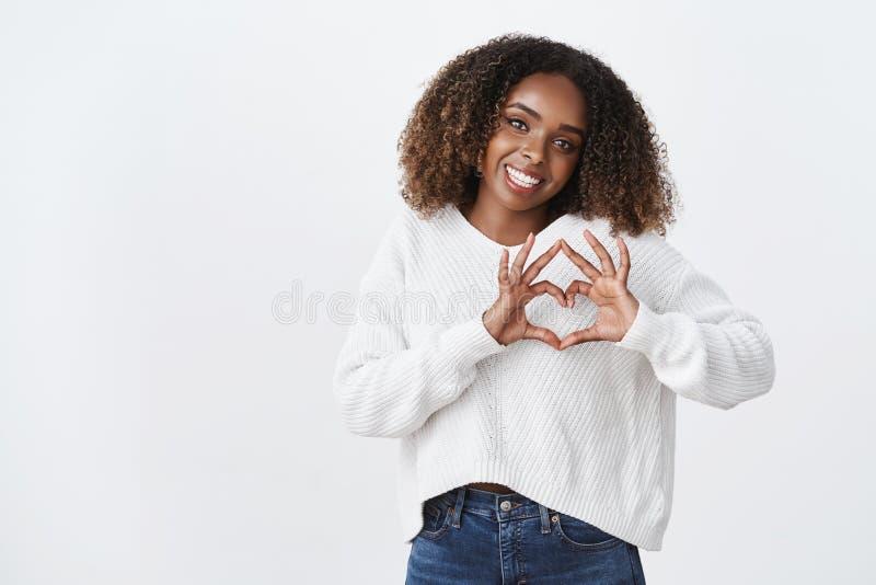 Lieben Sie Sie FRISURshowherzgesten-Neigungskopf der attraktiven dummen Afroamerikanerfrau Afro, derfroh lächelt stockfotos