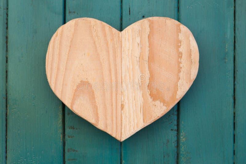 Lieben Sie hölzernes Herz der Valentinsgrüße auf Türkis gemaltem Hintergrund stockfotografie